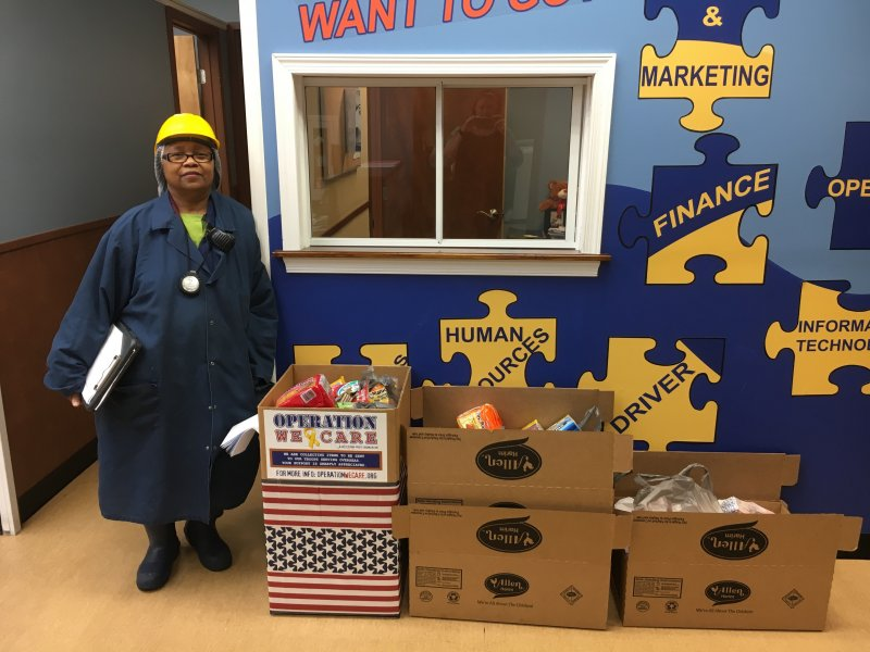 Allen Harim employee Rose Sher makes a donation at the company's Harbeson processing plant for Operation We Care.